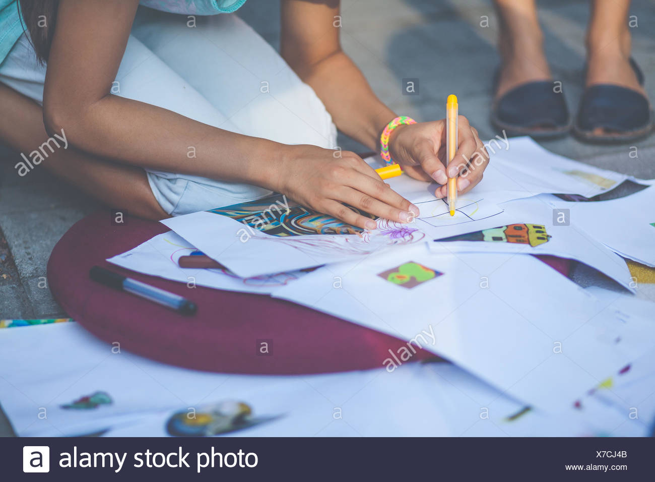 Girl kneeling on ground drawing - Stock Image