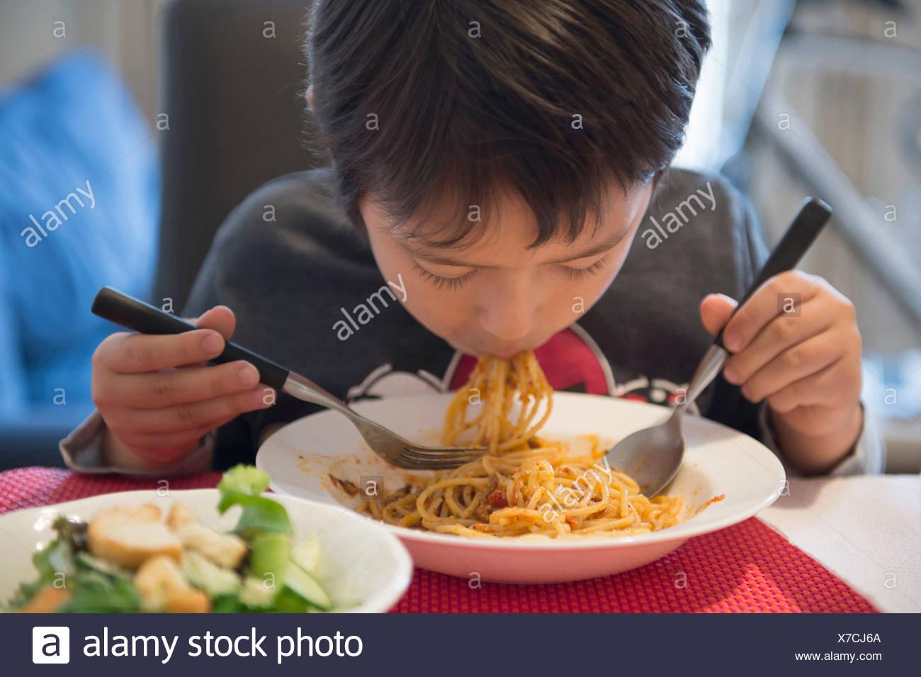 Boy eating spaghetti - Stock Image