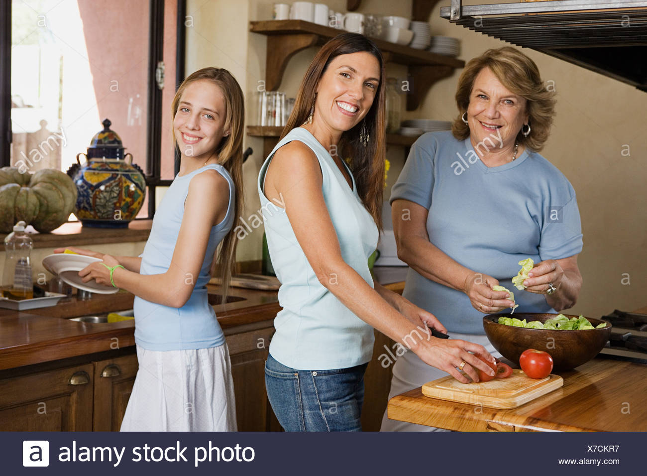 Female members of a family preparing a salad - Stock Image