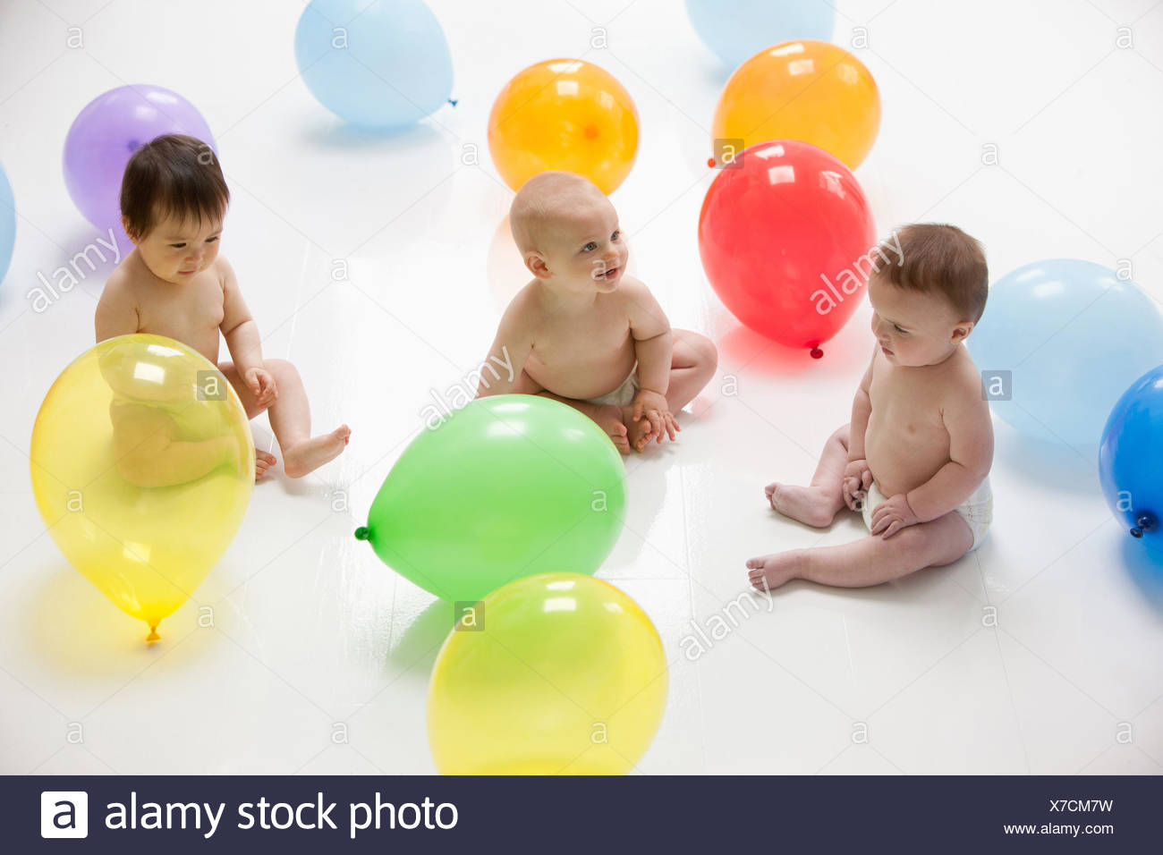 Babies with balloons on floor - Stock Image