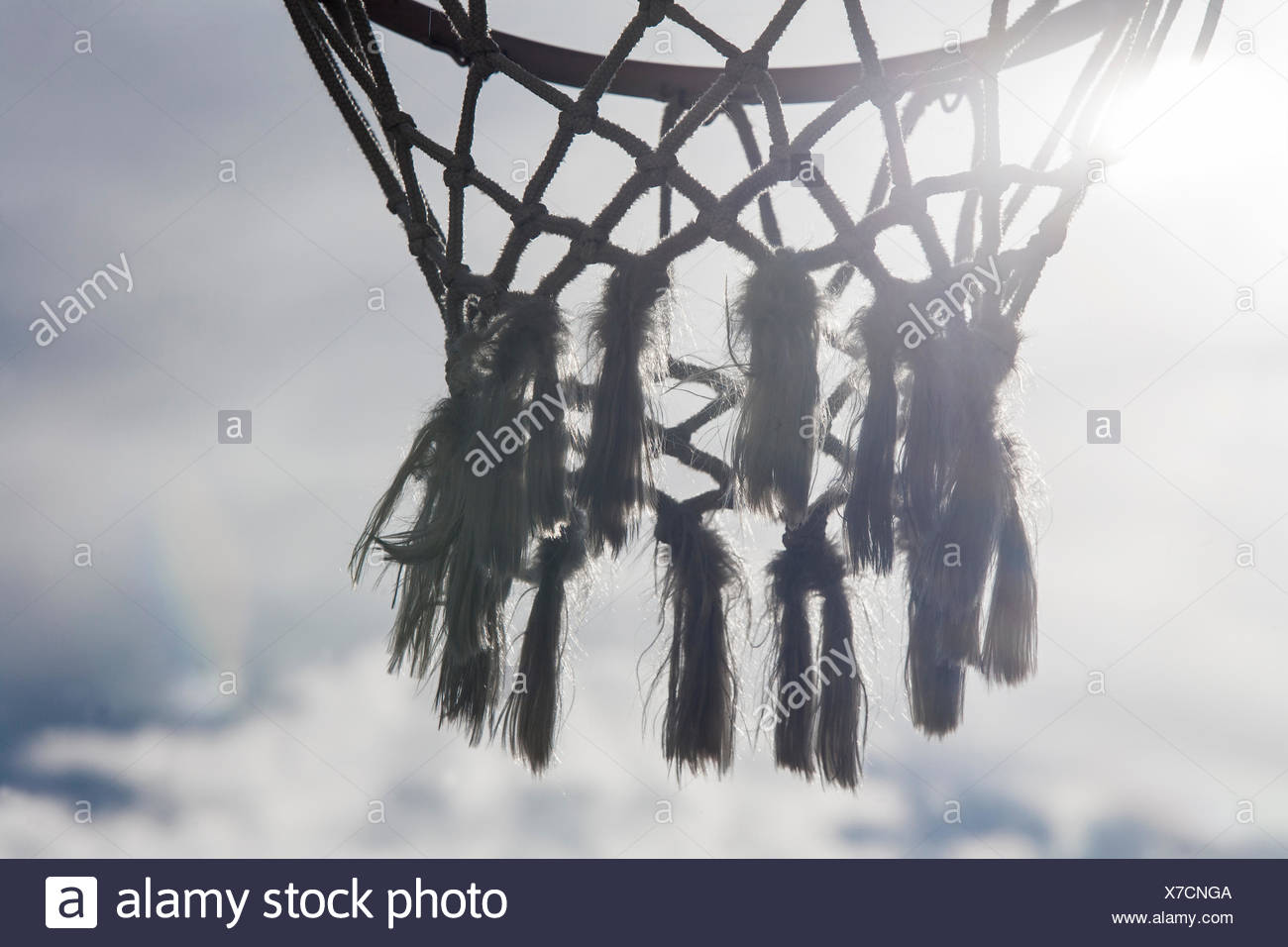Basketball hoop crossed by sun rays - Stock Image