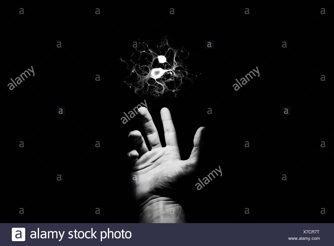 Outstretched hand reaching towards electrical spark - Stock Image
