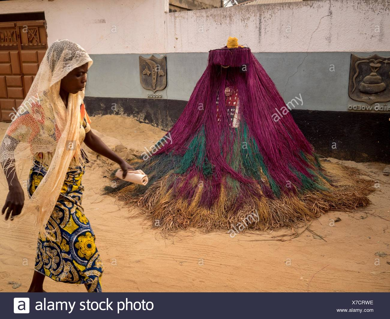 A woman walking in front of a Zangbeto mask, known as a 'Nightwatchman,' the traditional voodoo guardian of the night in the Yoruba religion of Benin and Togo. - Stock Image