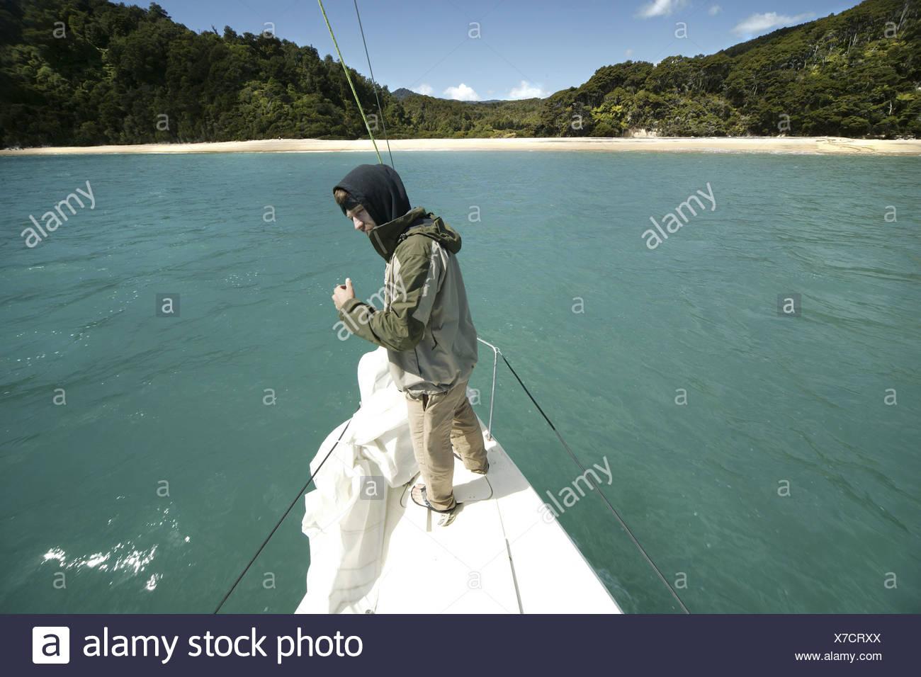 man at bow of a sailboat - Stock Image