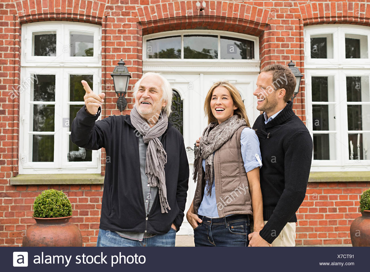 Father and mid adult couple outside house Stock Photo