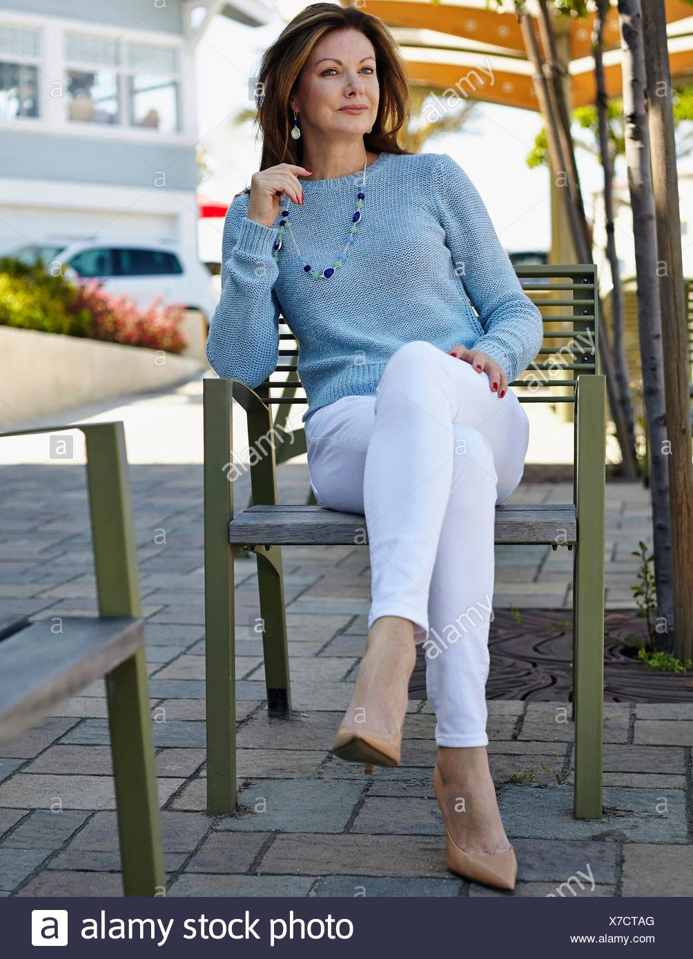 Portrait of elegant mature woman sitting on patio chair - Stock Image