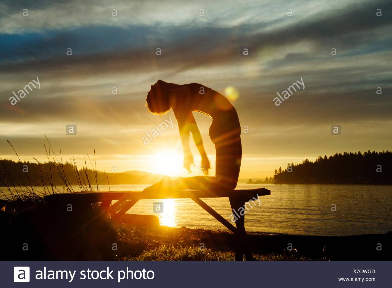 Woman practising yoga by lake at sunset Stock Photo