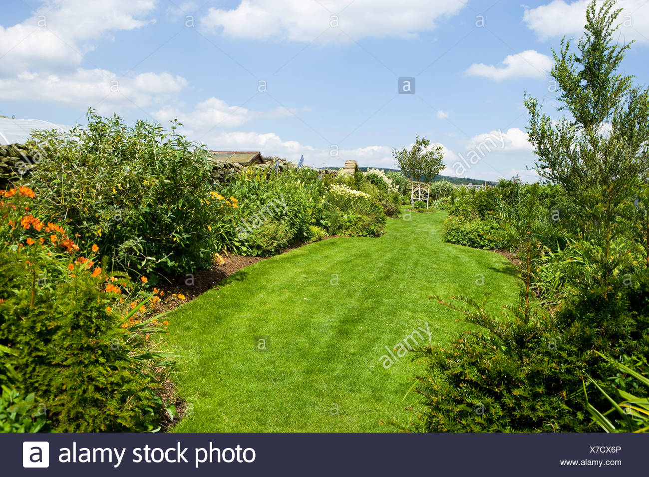 a windswept country garden with borders and beds. - Stock Image