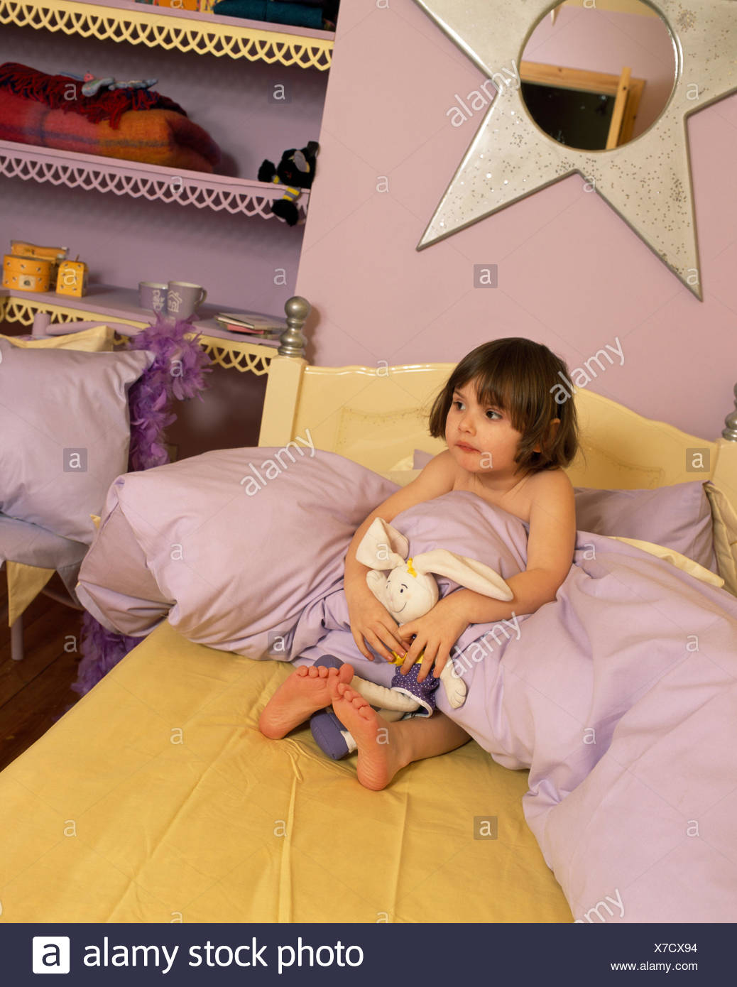 A small girl wrapped in a lilac duvet and sitting on the bed in a star themed bedroom - Stock Image