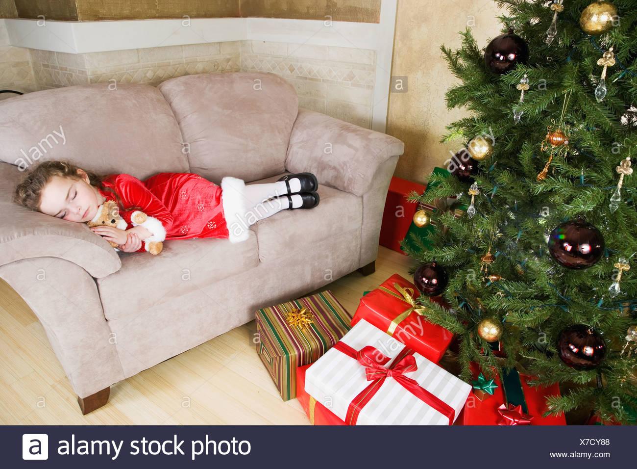 Girl (6-7) sleeping on sofa by Christmas tree Stock Photo