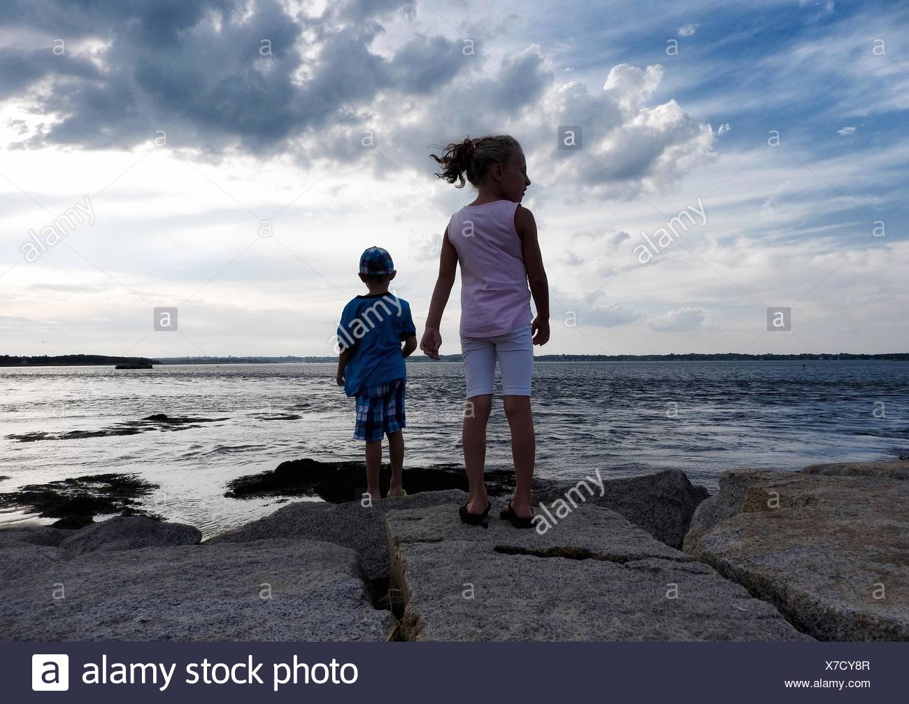 Rear View Of Siblings Standing On Rocks At Seaside Against Cloudy Sky - Stock Image
