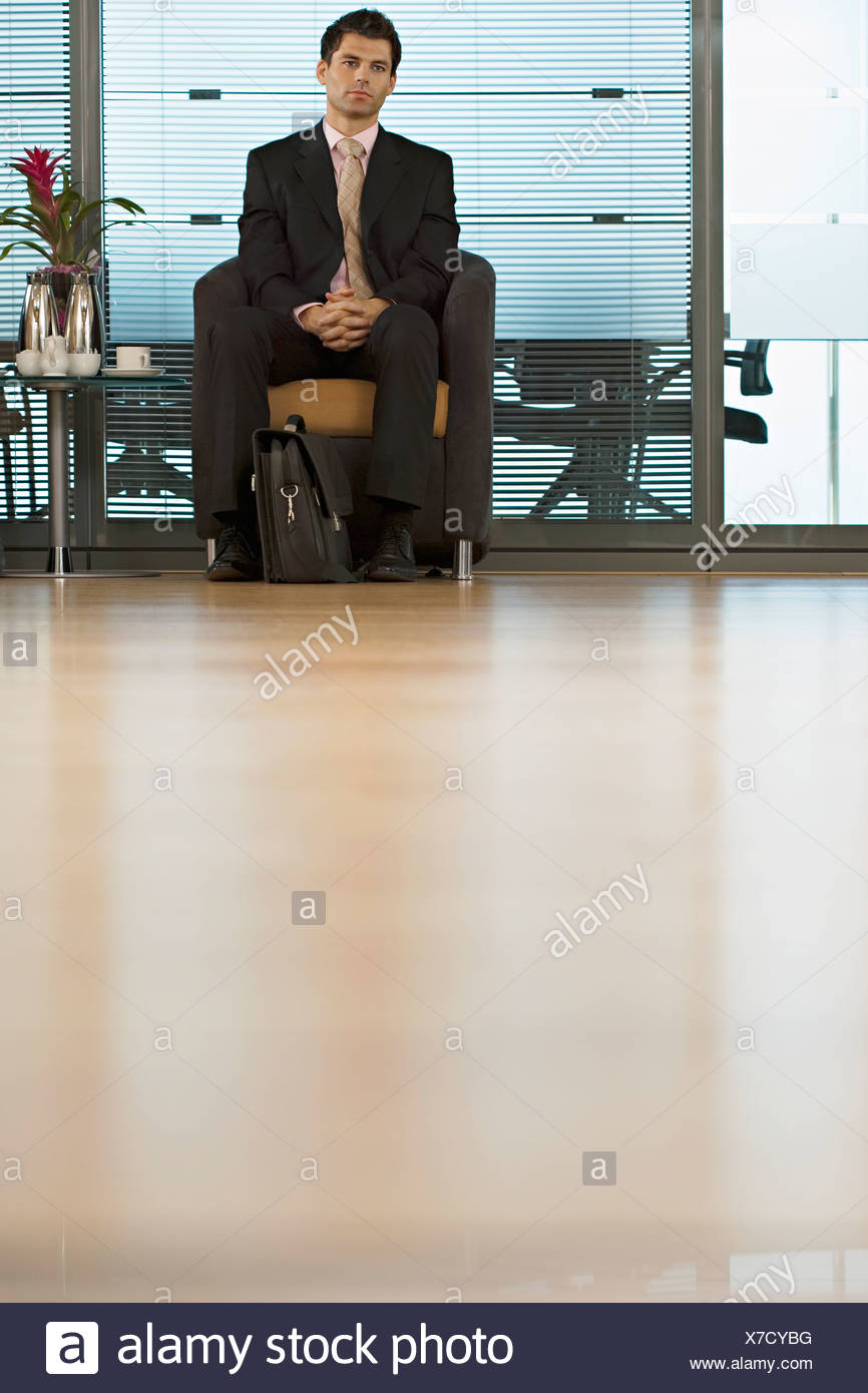Businessman sitting in office reception area waiting patiently front view surface level - Stock Image