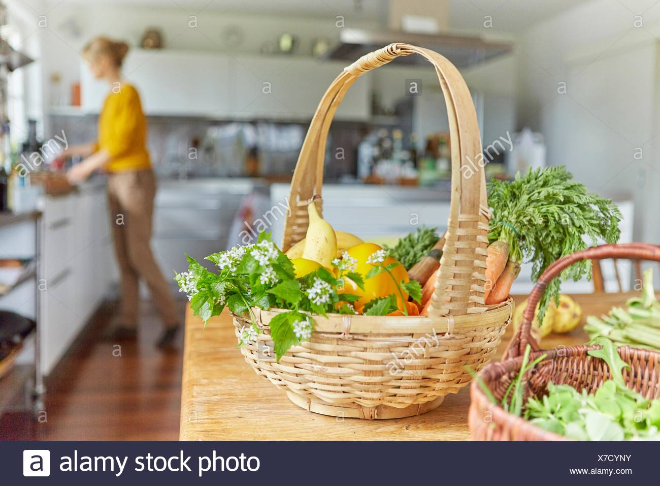 Garden produce, in baskets on table in kitchen, mature woman working in background - Stock Image