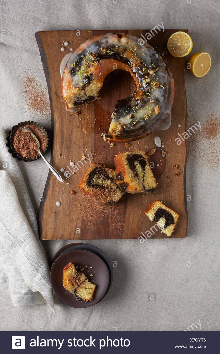 Chocolate and Lemon Swirl Bundt Cake on a Bark Lined Wood Cutting Board - Stock Image