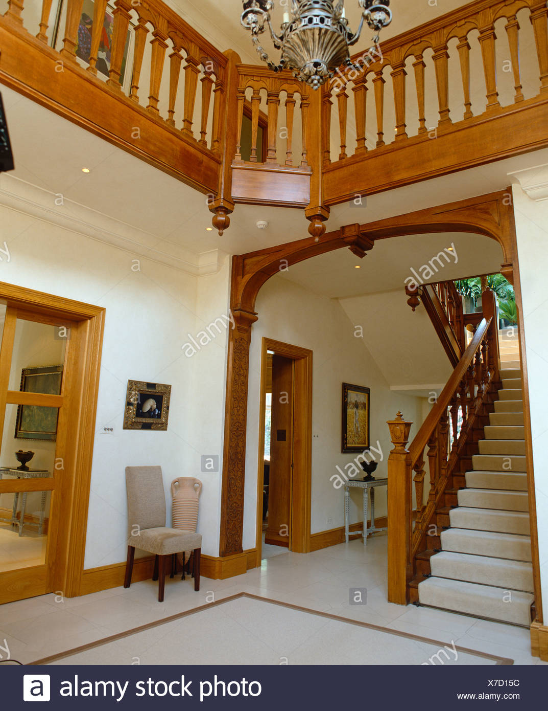 White carpet on wooden staircase in double height hall with carved wooden banisters on landing Stock Photo