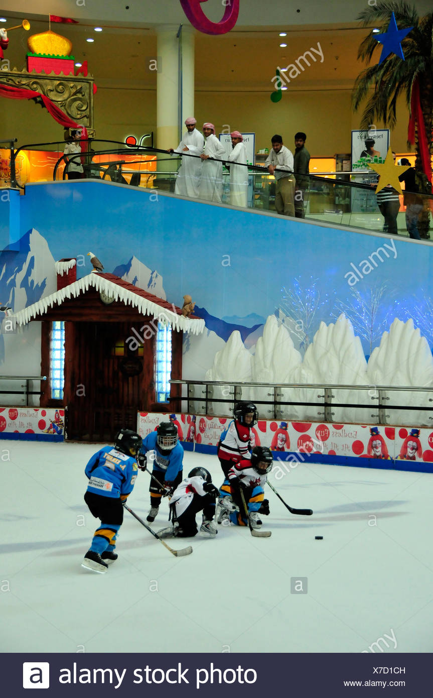 Arabs in Dishdashas, the typical white garments, watching kids playing ice hockey on the ice rink of the Al Ain Mall, Al Ain, A - Stock Image