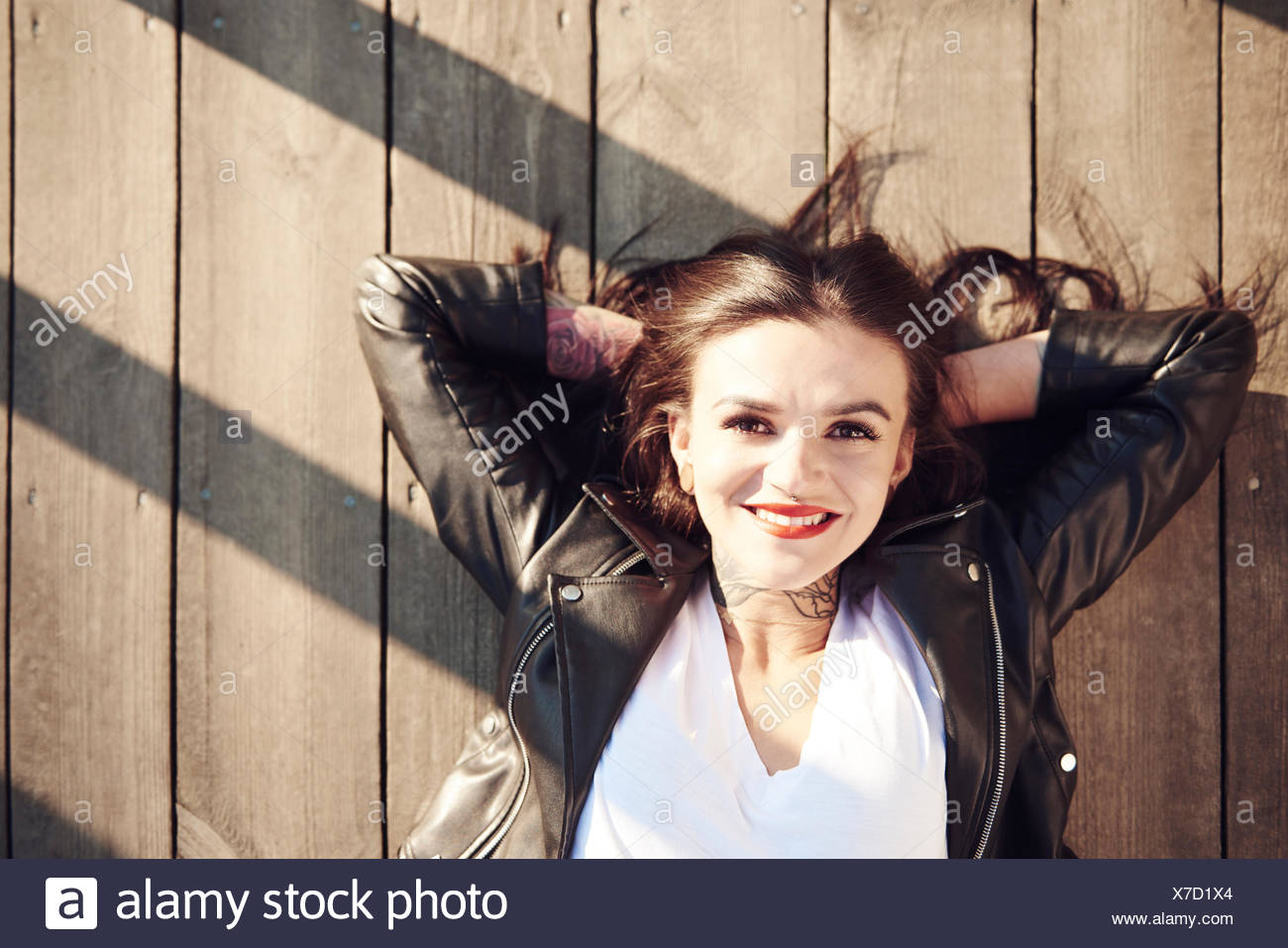 Portrait of young woman lying on wooden decking, hands behind head, smiling, overhead view - Stock Image