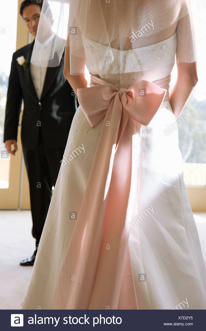 Bride wearing wedding dress with pink bow and veil, focus on groom standing in background, portrait - Stock Photo