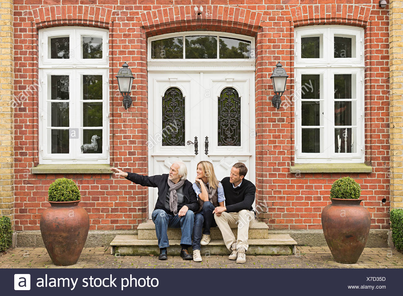 Father and mid adult couple sitting on doorstep Stock Photo
