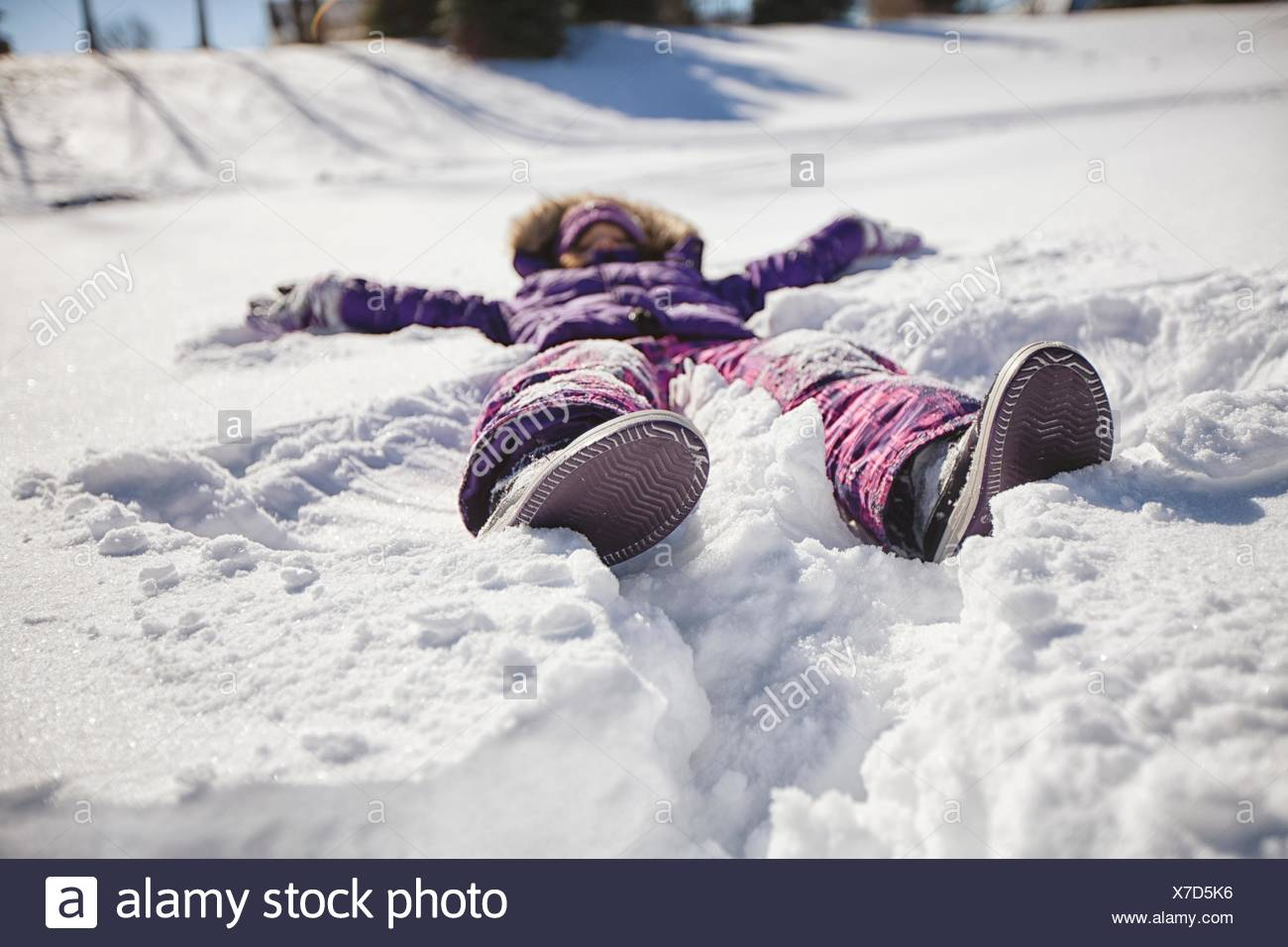 Surface level view of girl wearing ski suit lying snow making snow angel - Stock Image