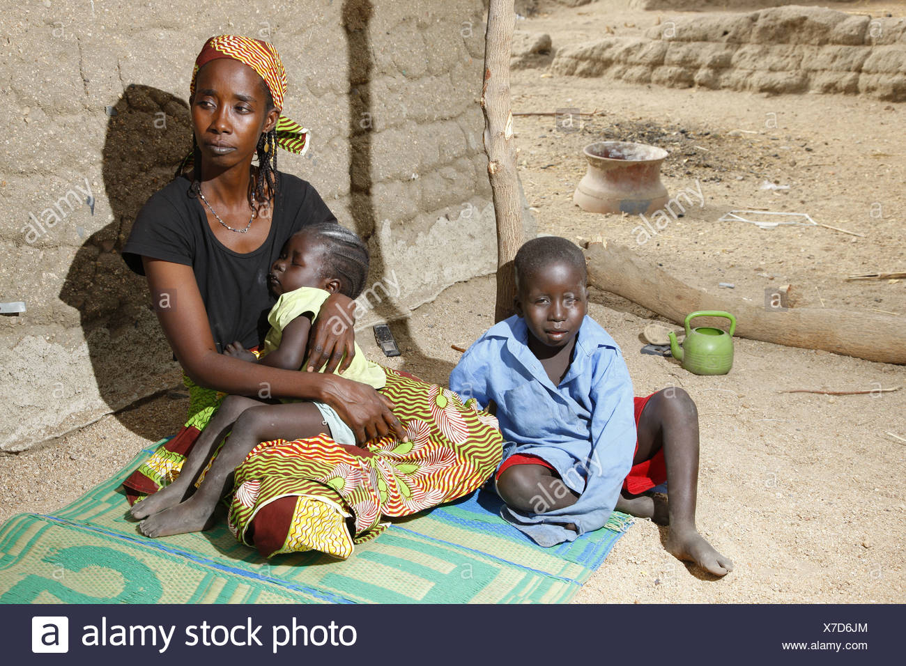 Woman and her two children seated in front of a house, Maroua, Cameroon, Africa - Stock Image