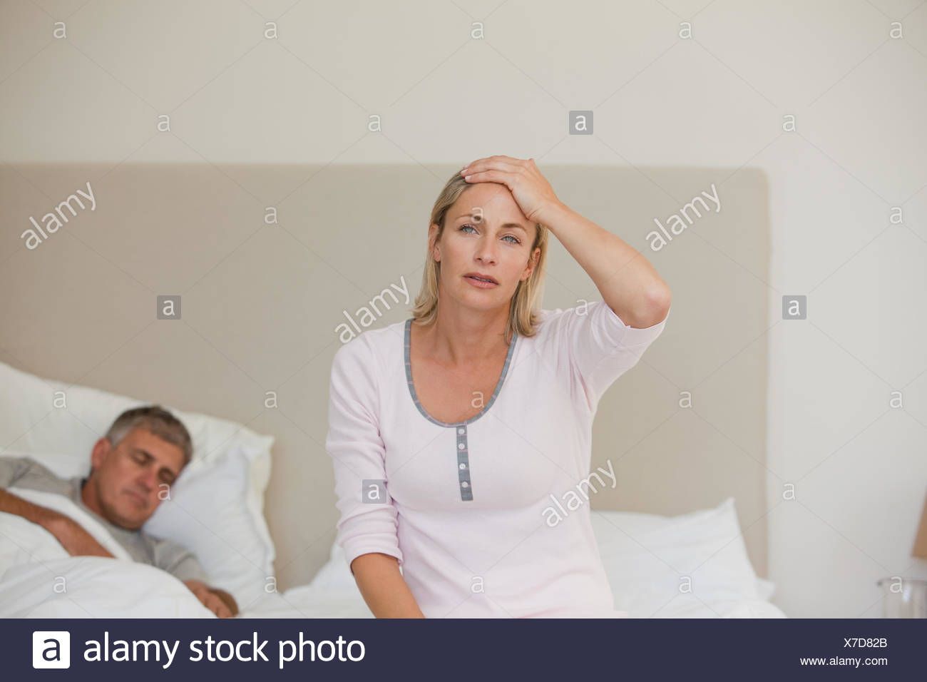 Woman having a headache while her husband is sleeping Stock Photo