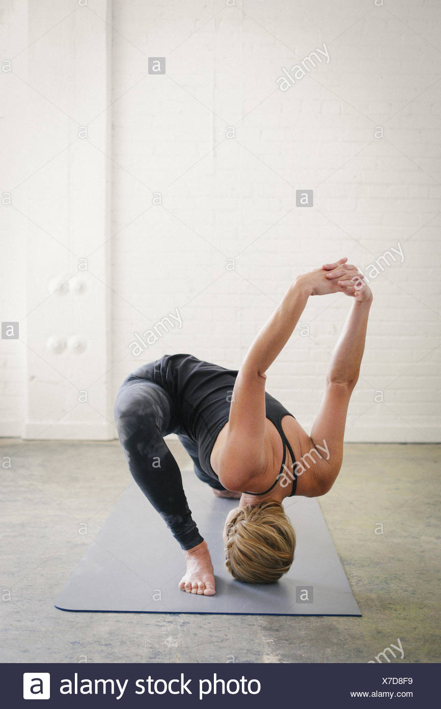 A blonde woman doing yoga, kneeling with her legs apart and her arms raised. - Stock Image