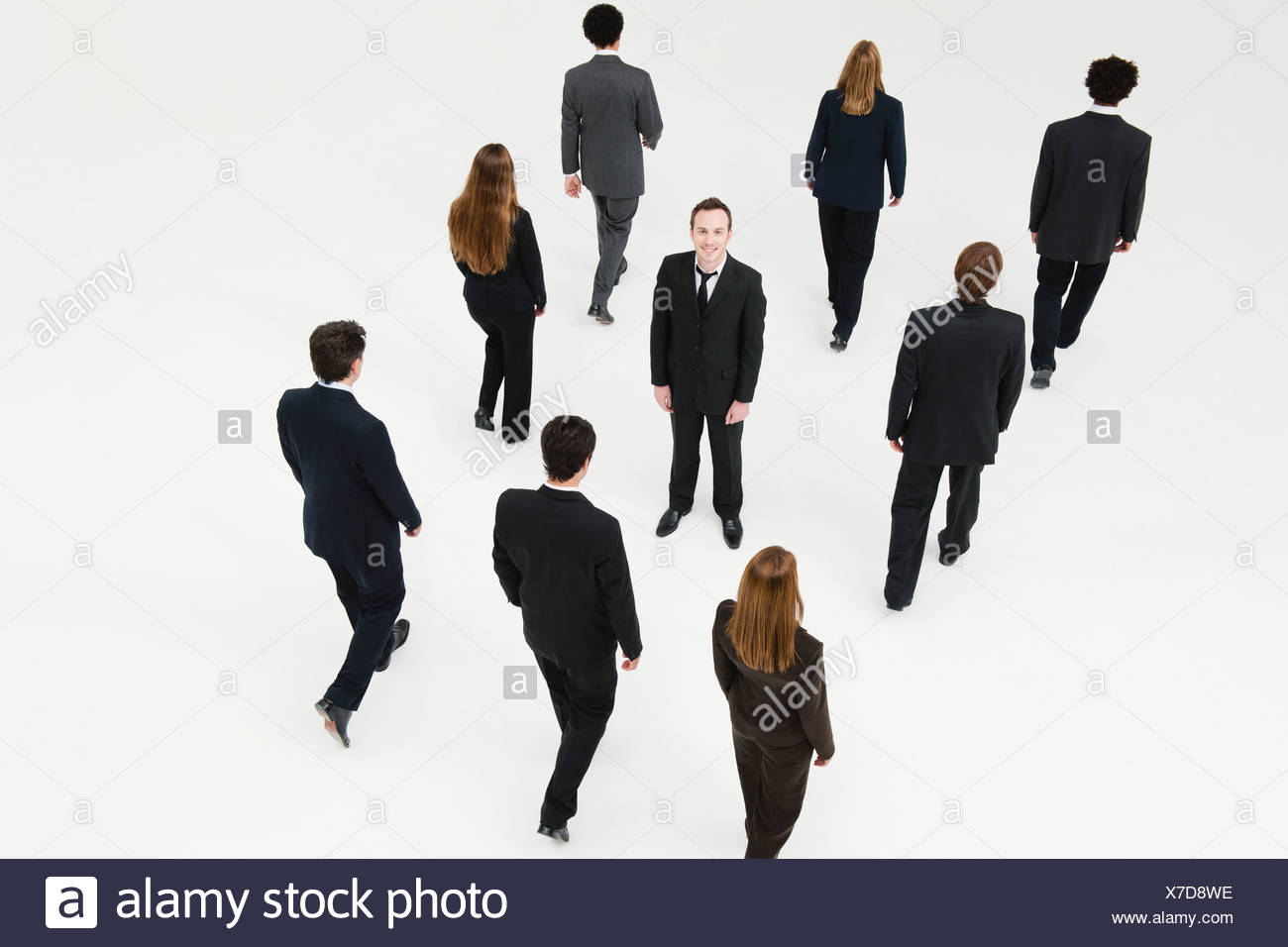 Businessman standing in midst of other anonymously dressed business professionals - Stock Image