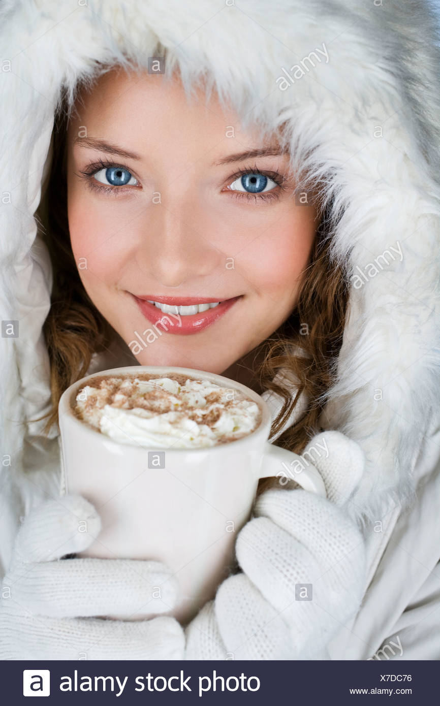 A young woman wearing a winter coat, holding a mug of hot chocolate - Stock Image