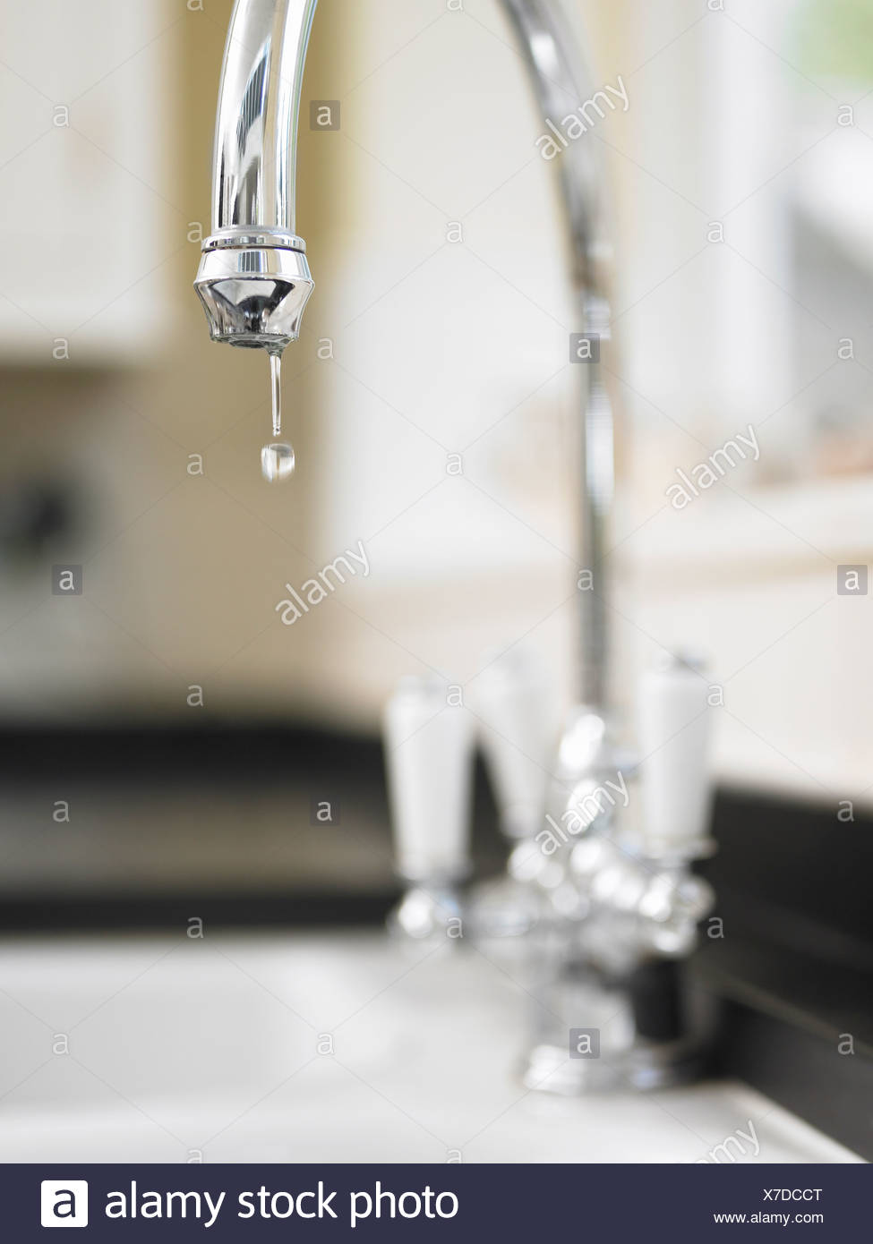 Close up of water droplet dripping from kitchen faucet - Stock Image