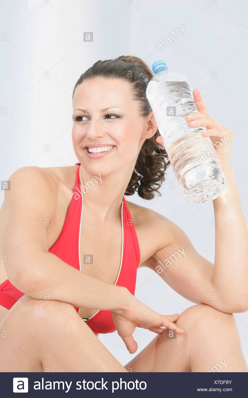 Young woman holding water bottle, smiling, portrait - Stock Image