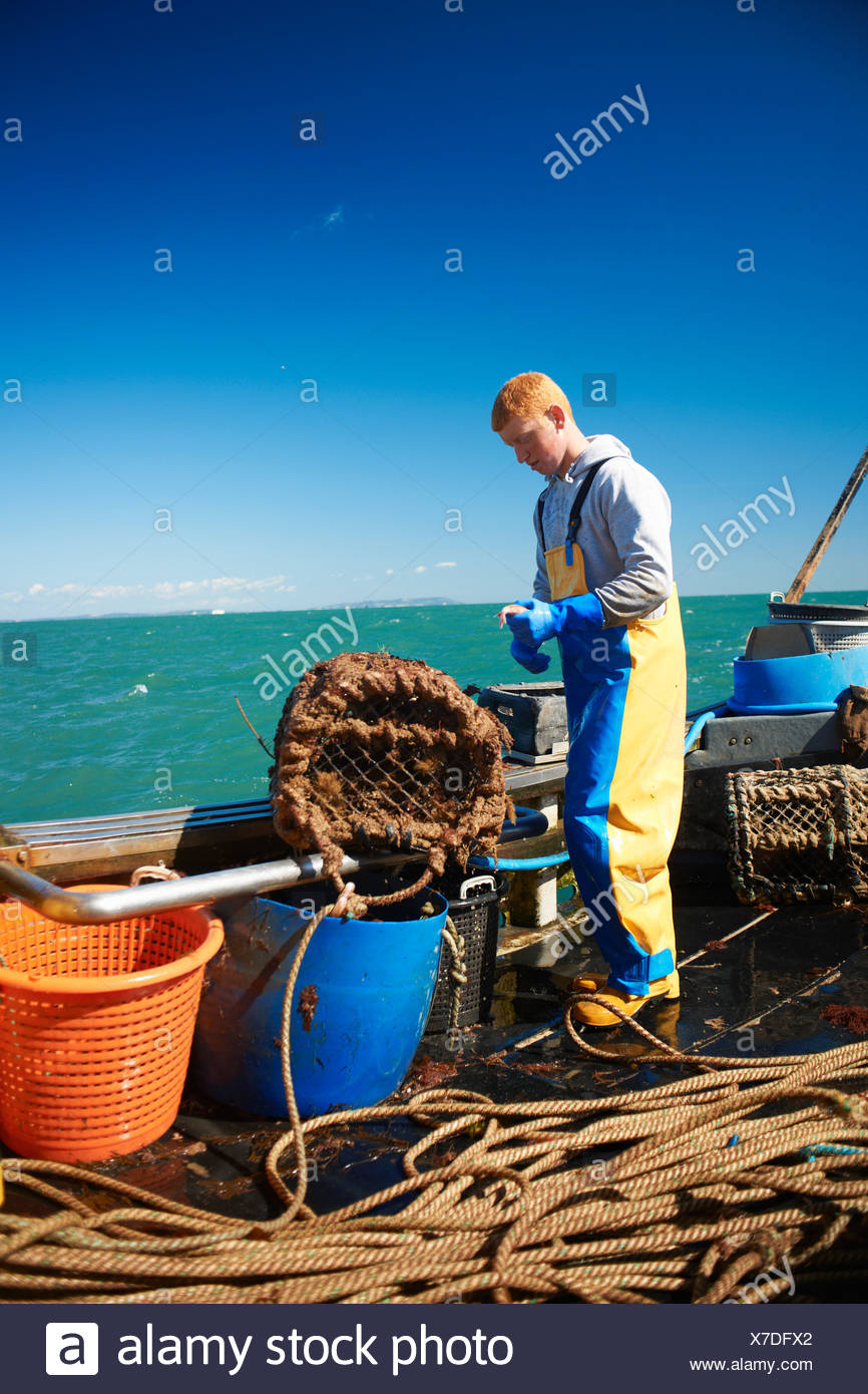 Fisherman at work on boat - Stock Image