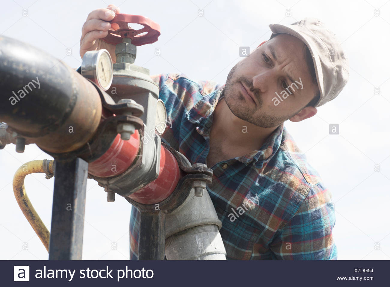 Man opening valve on industrial piping - Stock Image