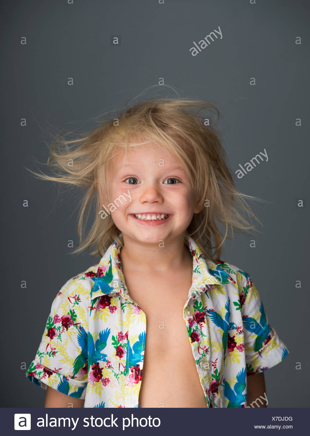Portrait of young boy with messy hair, smiling - Stock Image