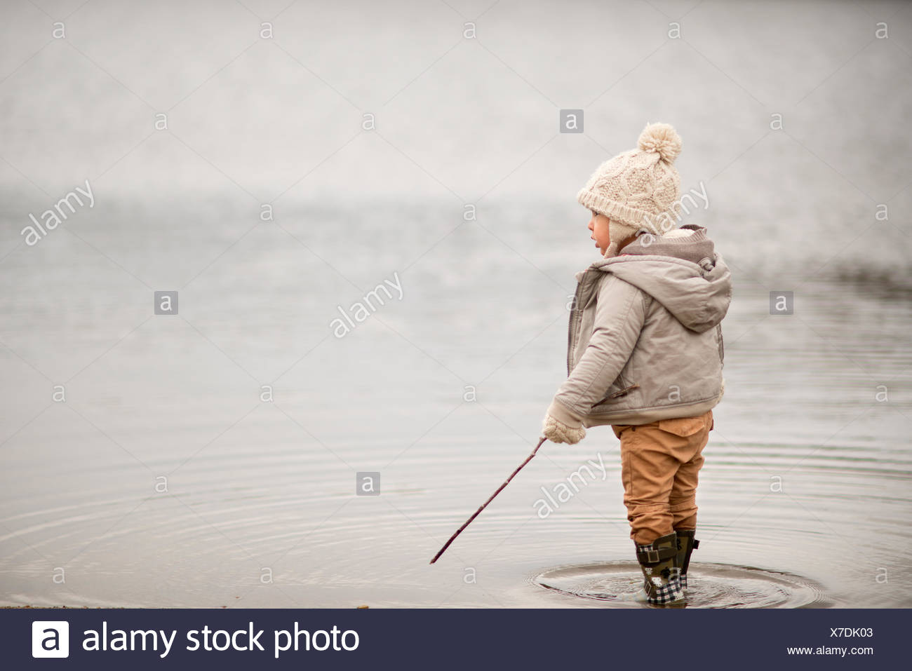 Young boy standing in a lake, holding a stick - Stock Image
