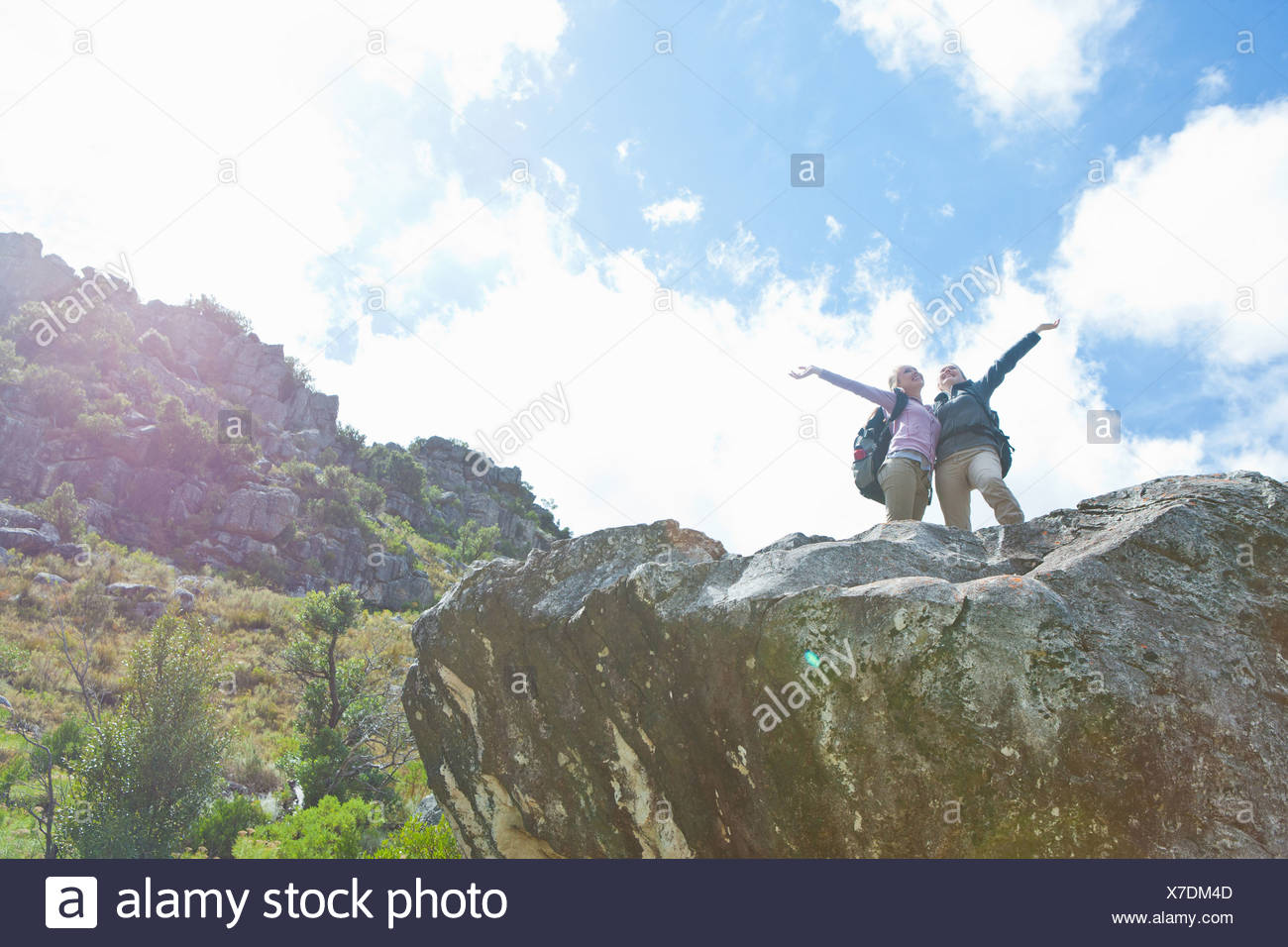 Two girl hikers celebrating on top of rock formation - Stock Image