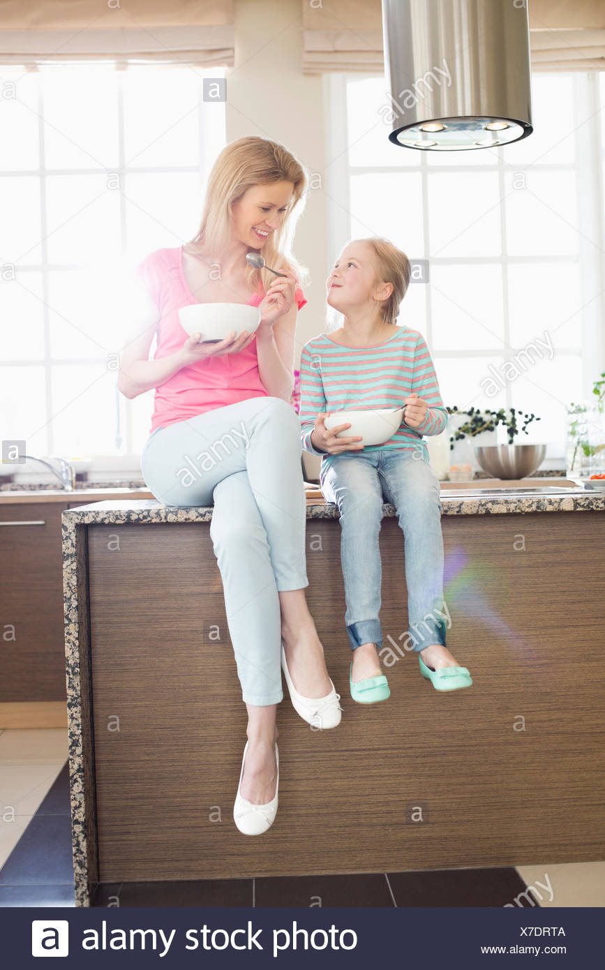 Mother and daughter looking at each other while having breakfast in kitchen - Stock Image