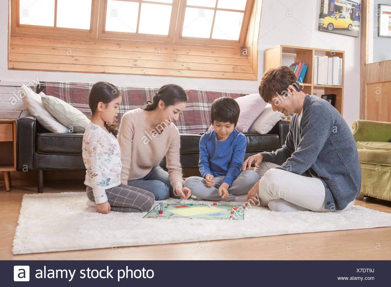 Harmonious family playing a board game together in living ...