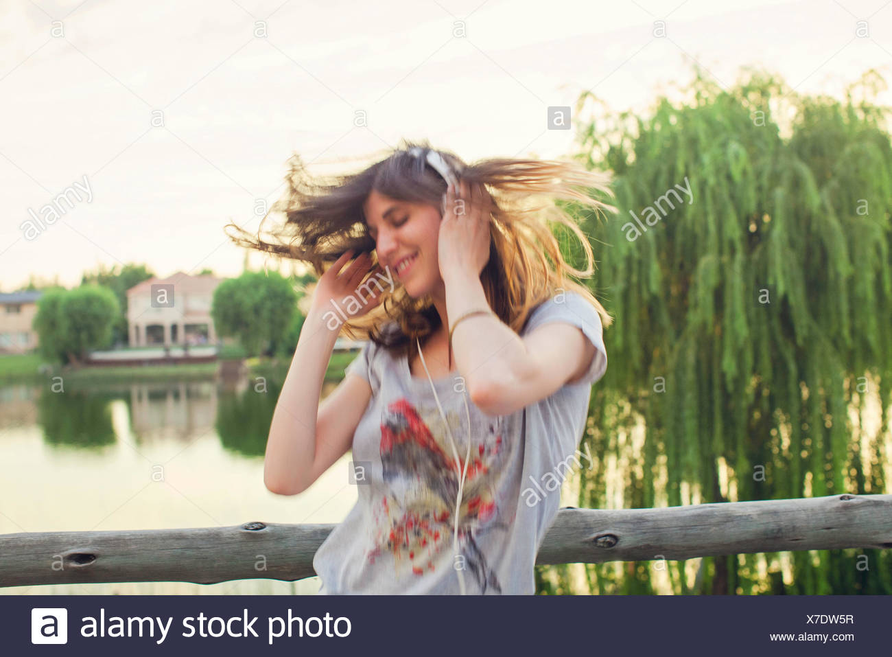 Young woman enthusiatically listening to music - Stock Image