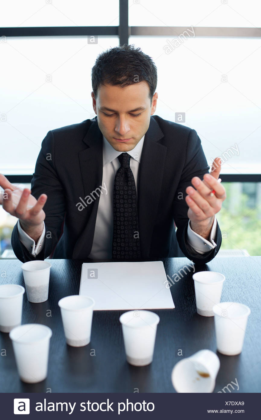 Reflective businessman sitting at table with plastic cups of coffee Stock Photo