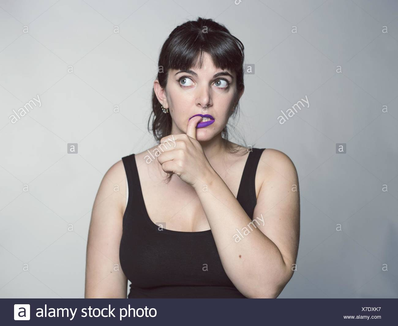 Studio Shot Of Young Woman Biting Her Nail - Stock Image