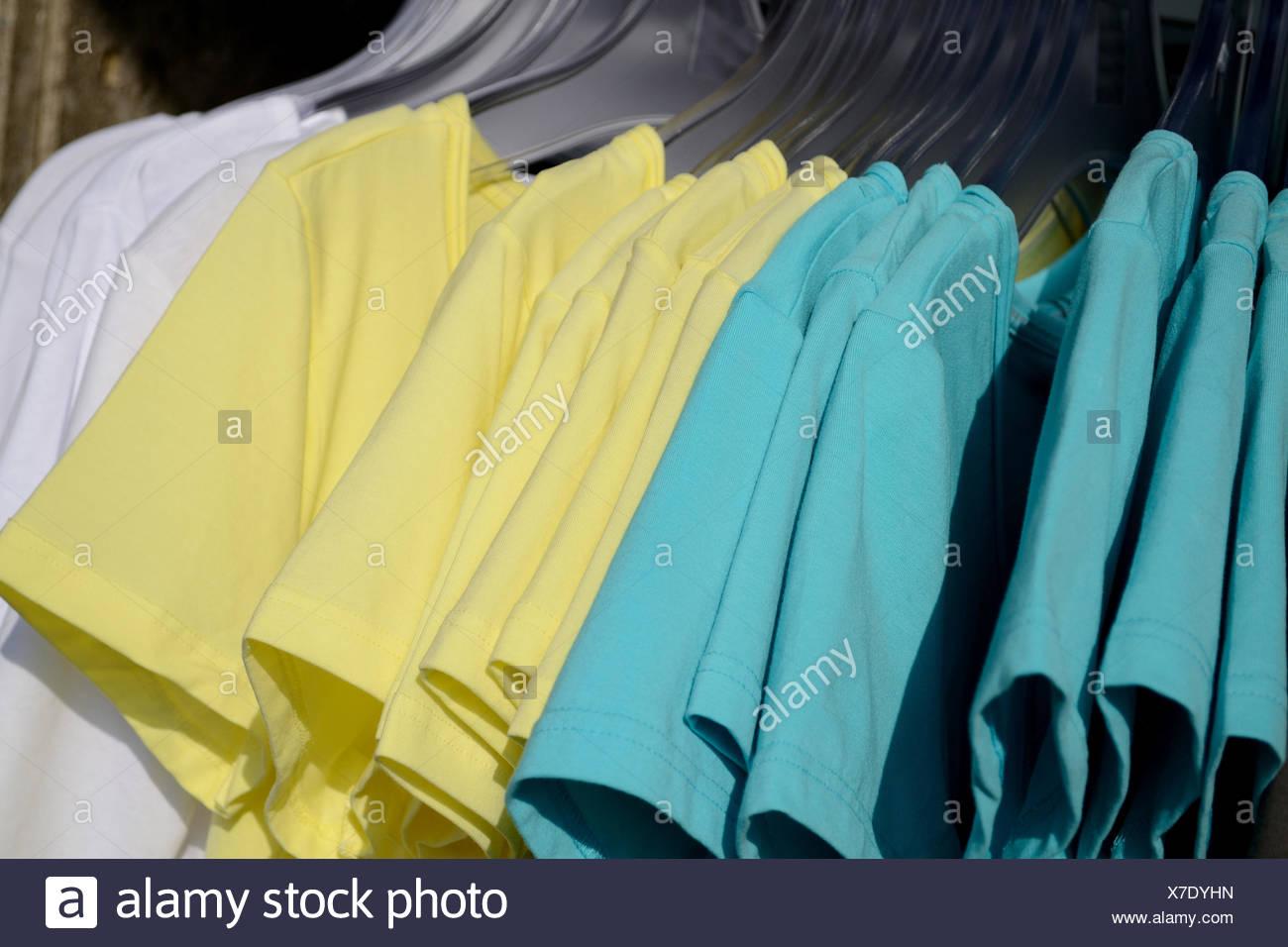 zahlreiche T-Shirts in mehreren Farben auf Kleiderstaender zur Auswahl - Stock Image