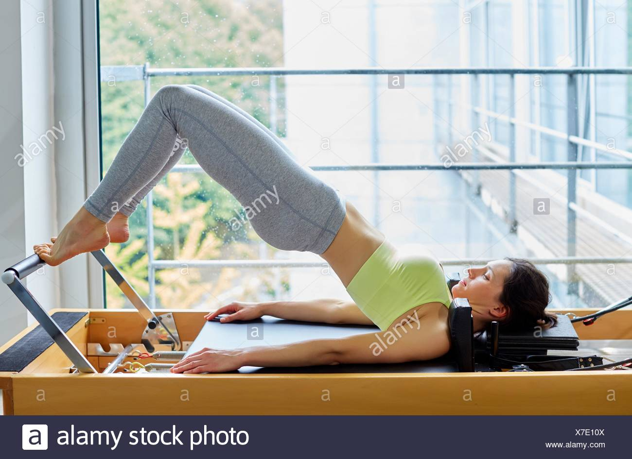 Pilates reformer, Woman training in gym - Stock Image