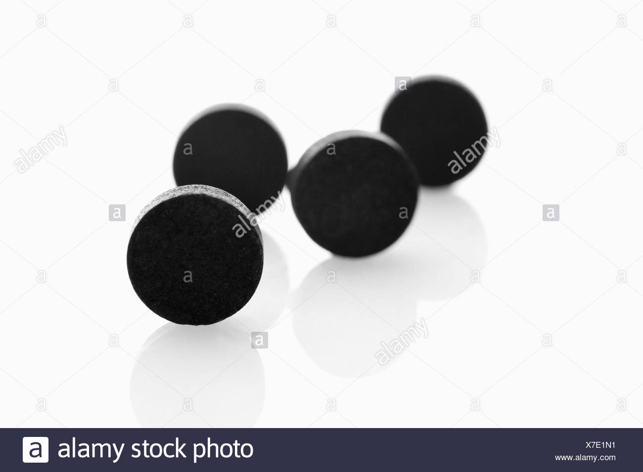 Black tablets on white background - Stock Image