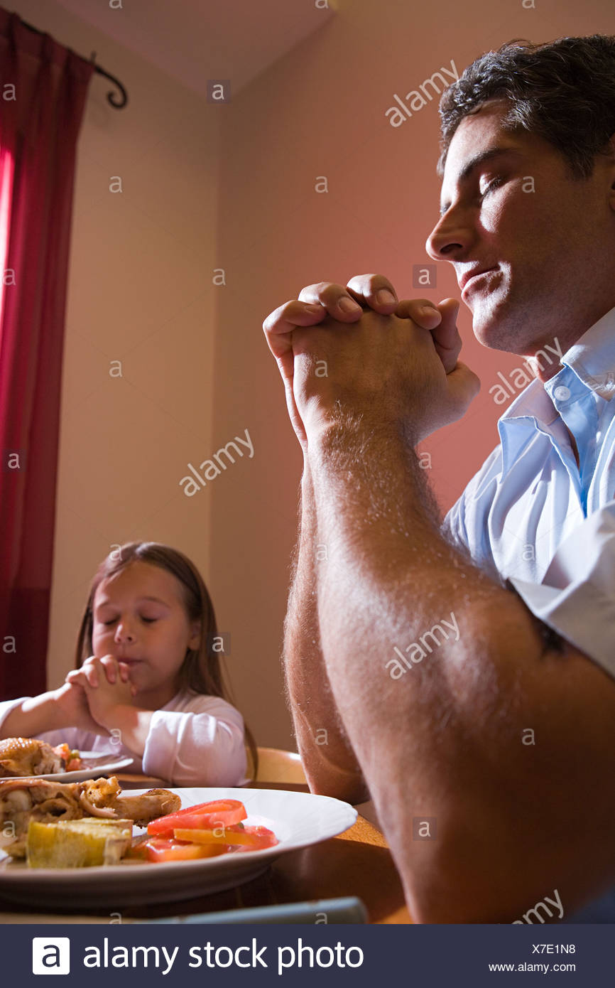 Father and daughter saying grace - Stock Image