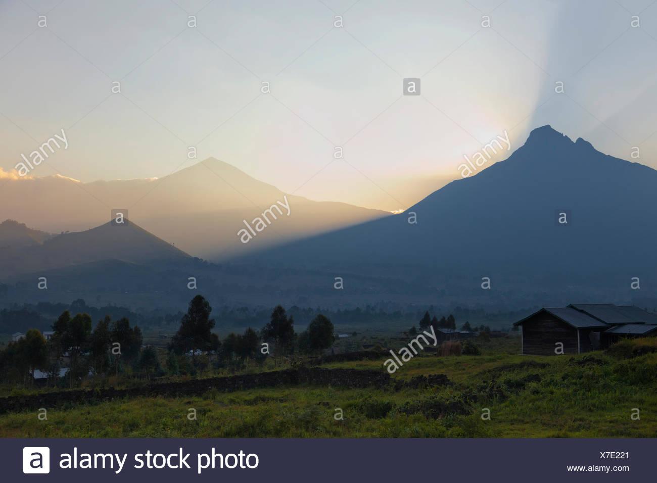 The Virunga volcanoes Mount Mikeno and Mount Karisimbi at sunrise - Stock Image