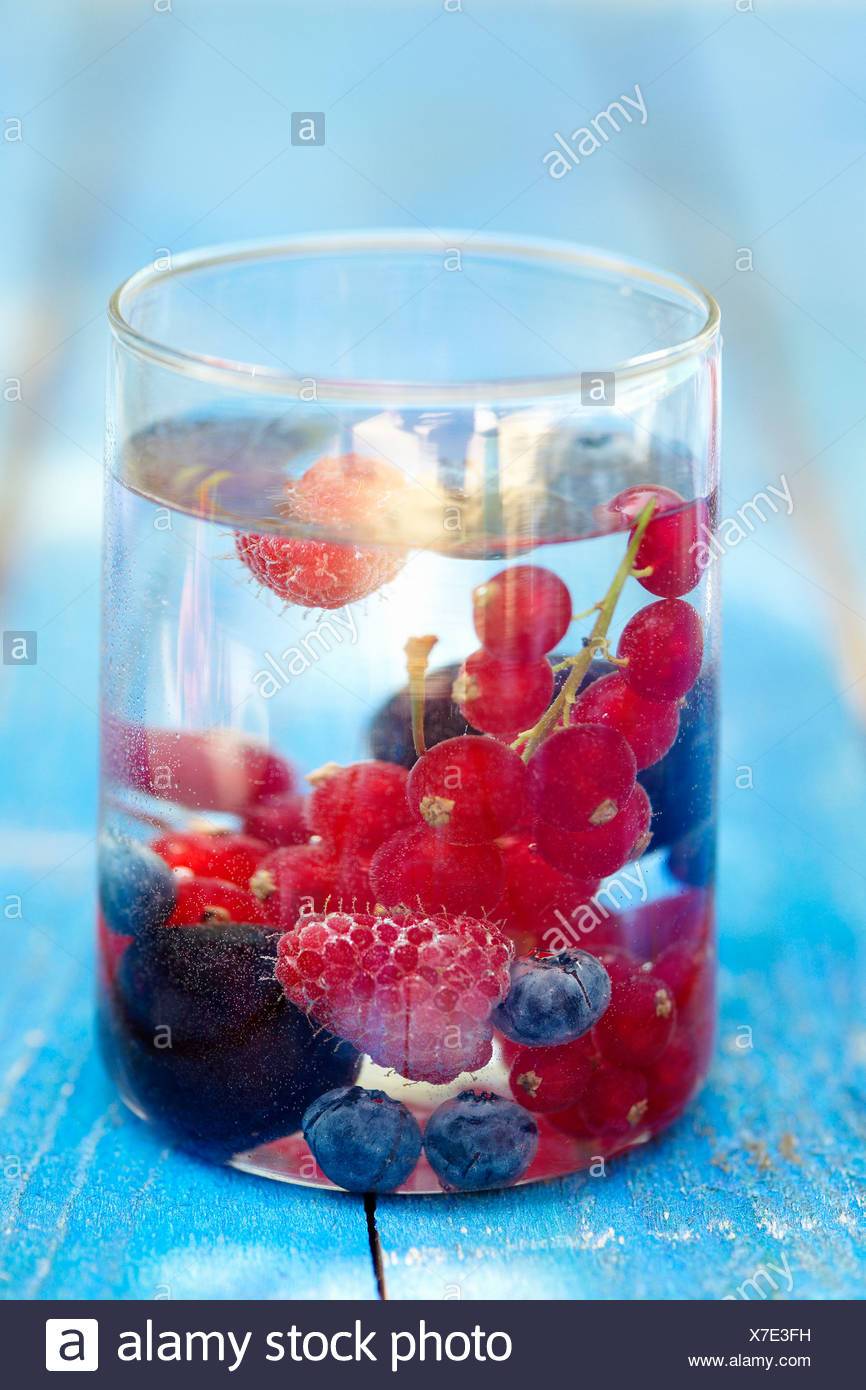 Summer fruit in a glass of water - Stock Image