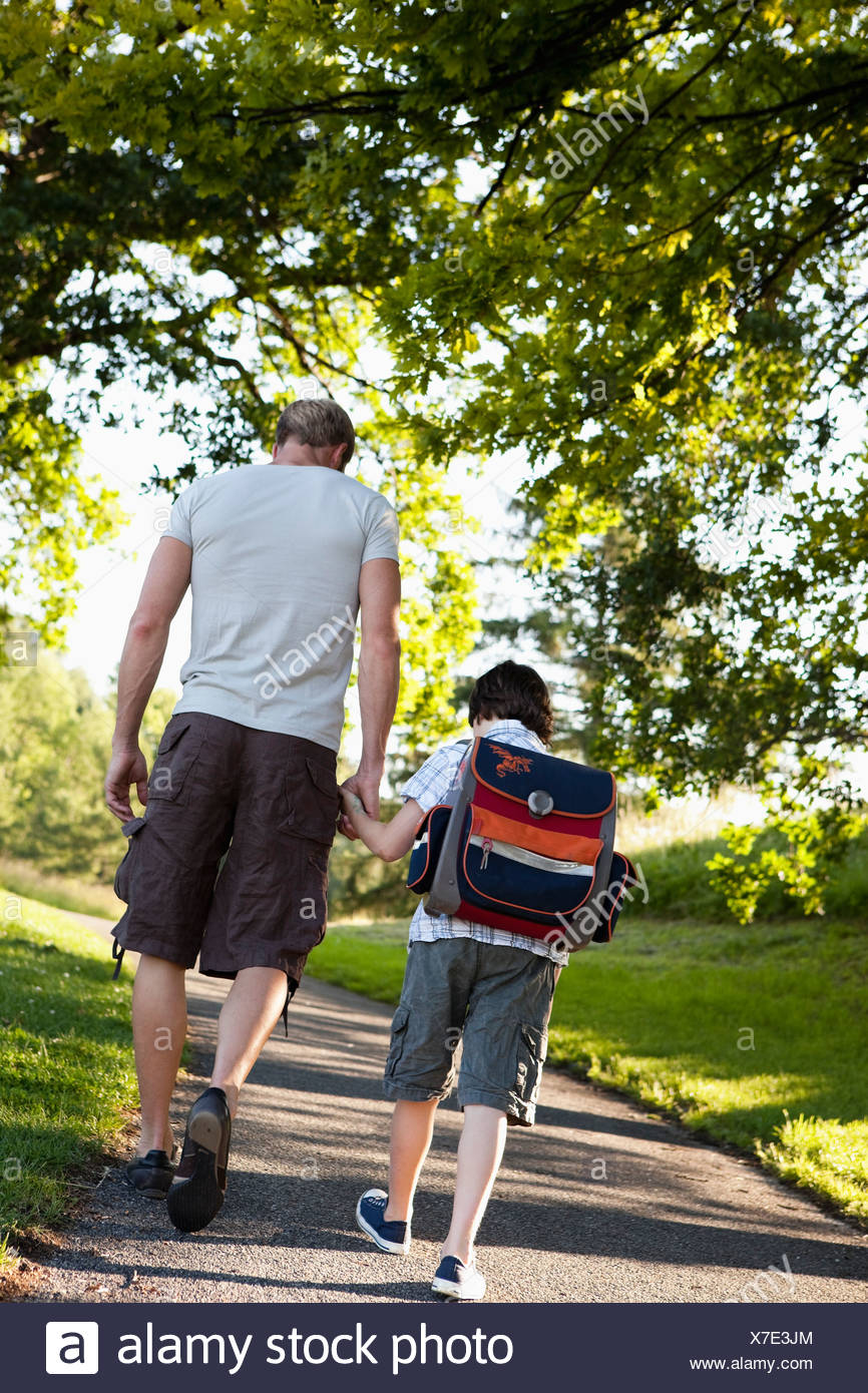 Father Walking Son To School - Stock Image