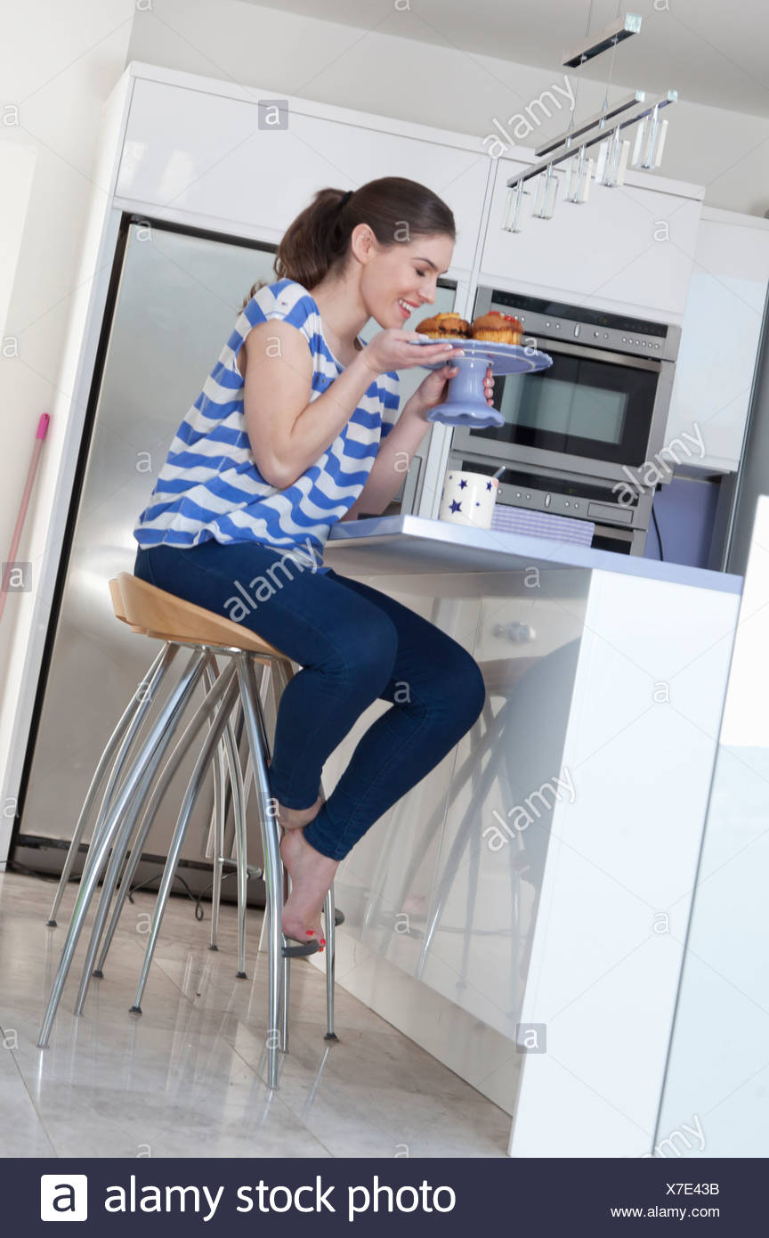 Young woman at breakfast bar smelling freshly baked cakes - Stock Image
