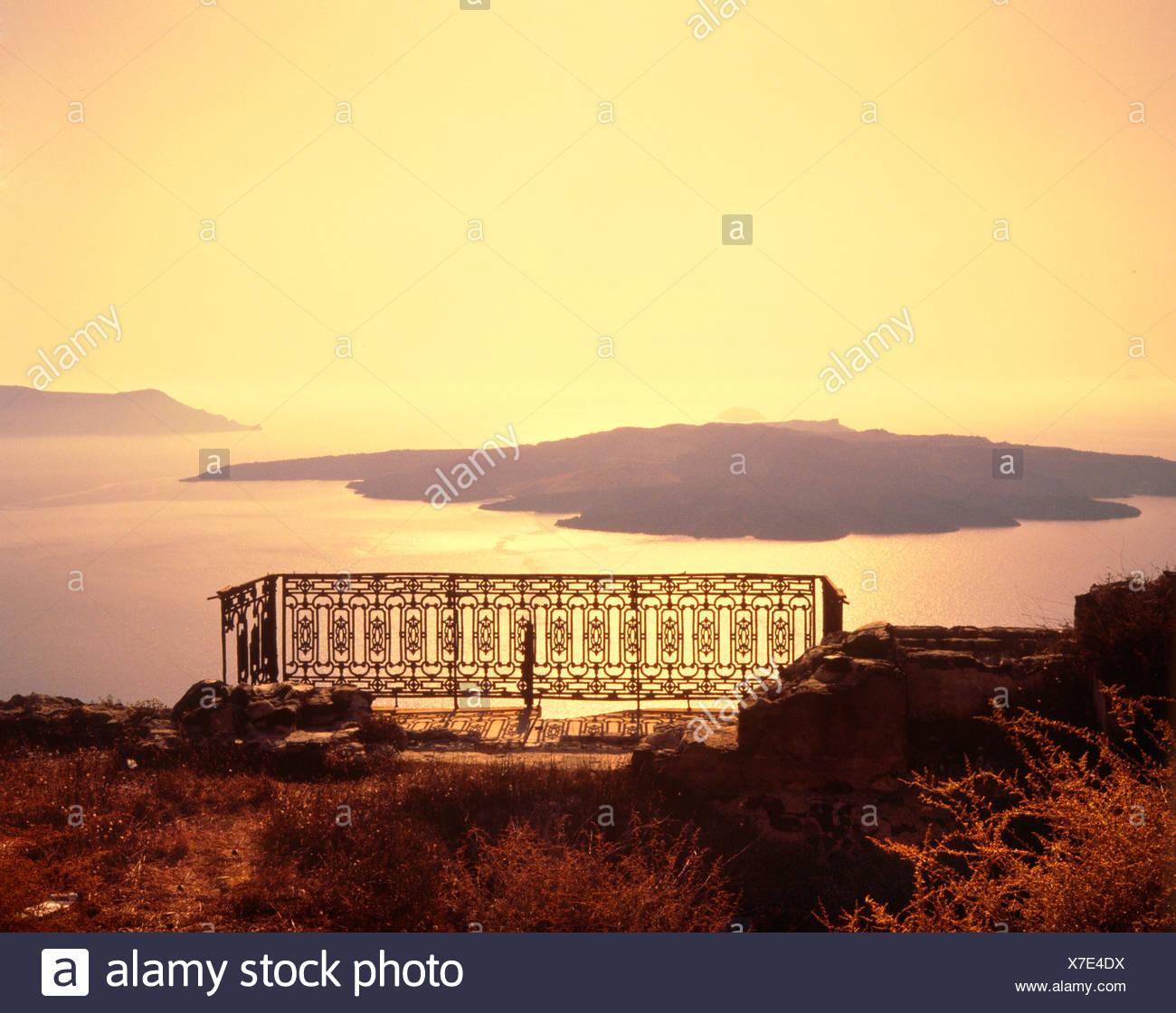 Volcanic island Nea Kameni in the caldera, over the balcony, the remains of a house after the earthquake of 1956, historic phot - Stock Image